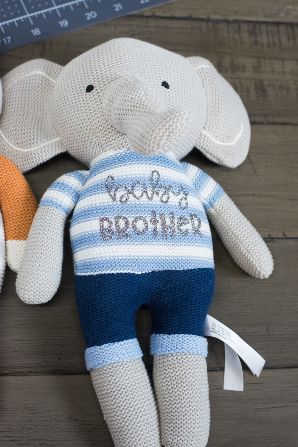 stuffed knit elephant with baby brother on the front in silver