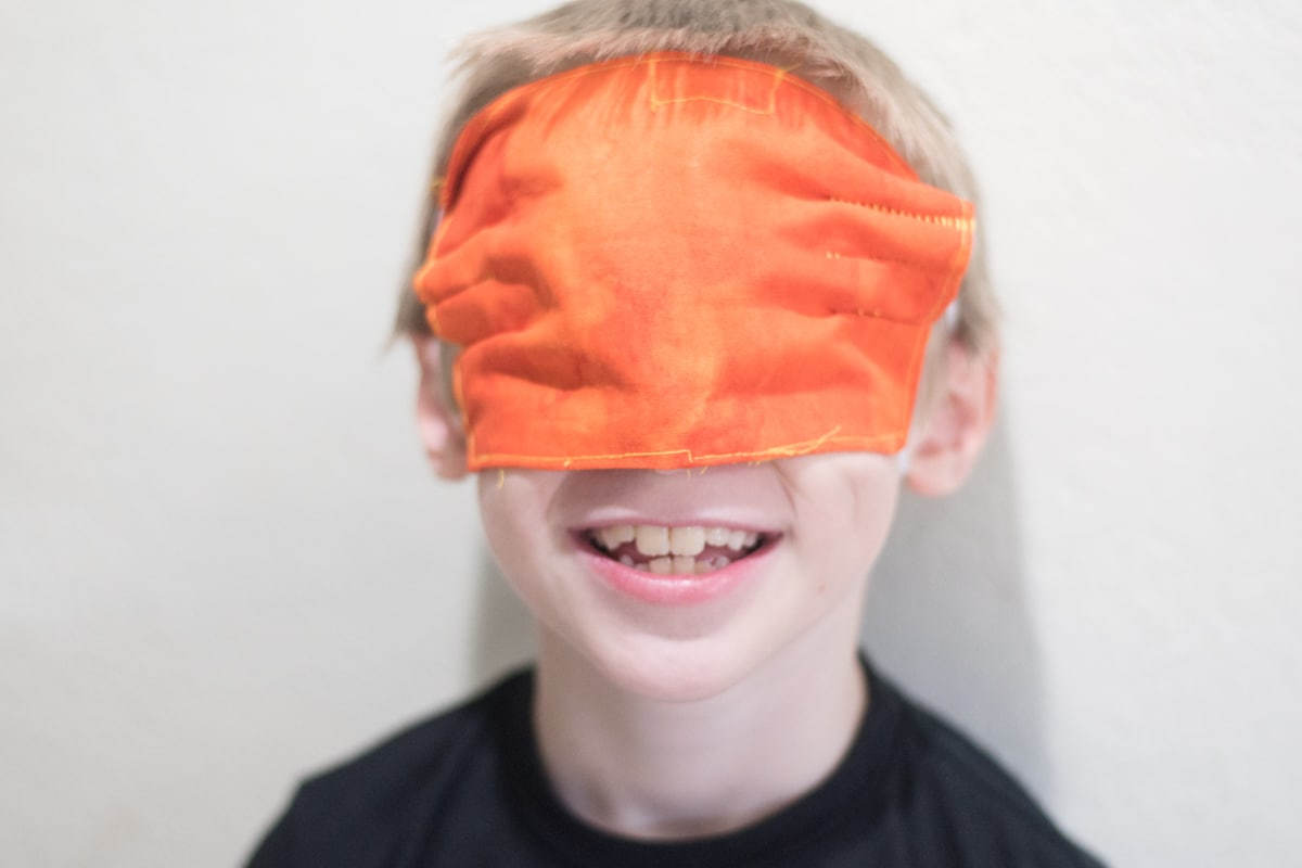 A young boy wearing a mask on eyes and smiling at the camera