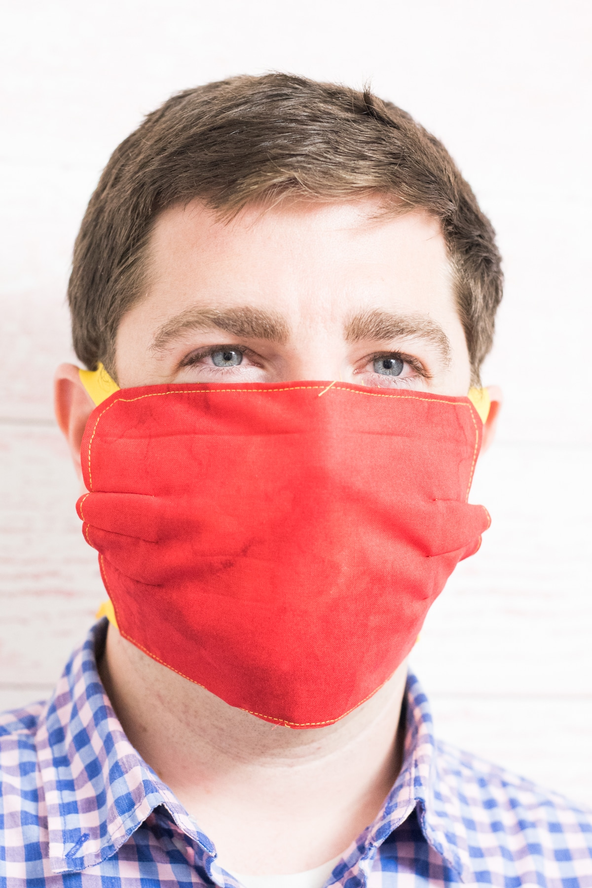 A close up of a man wearing a red mask and blue shirt