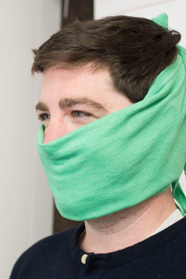 A close up of a man wearing t shirt face mask
