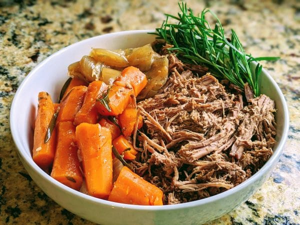 roast beef with carrots and onions and rosemary in bowl