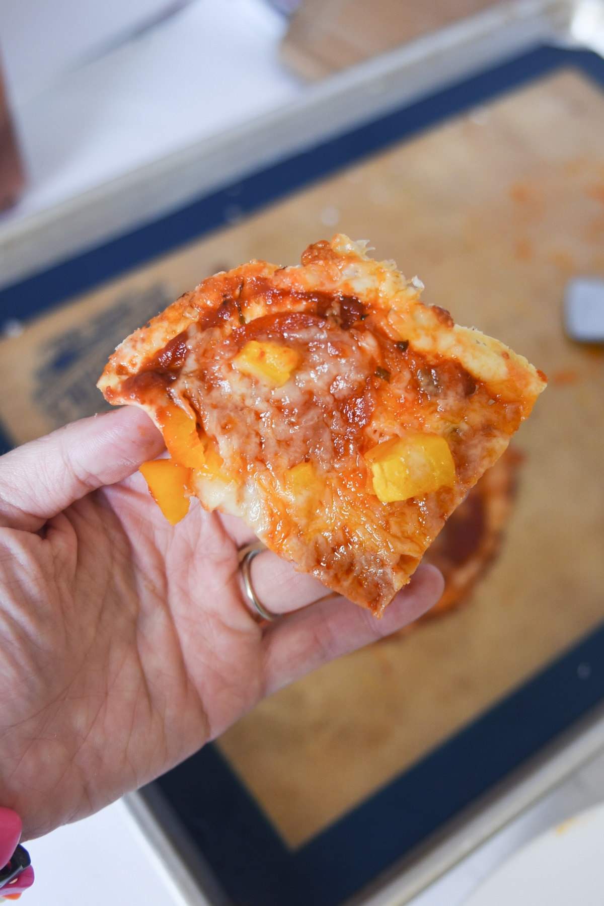 Easy Keto Pizza Crust made with Crystal Farms Cheese. This photo shows a slice of pizza with pepperoni and yellow peppers.