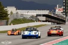 Una barqueta Lola junto a tres Porsche 911.
