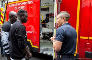 Mamoudou Gassama, second left, visits the Paris Fire Brigade headquarters and Champerret fire station in Paris on Tuesday. — AFP