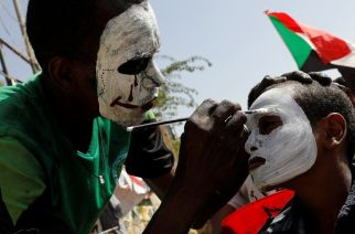 On that same day, over at the military headquarters, one demonstrator helps paint another's face.