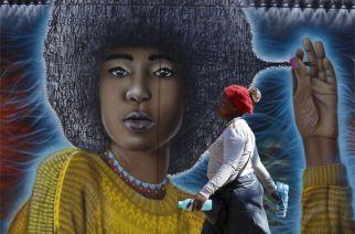 A woman walks past this mural in Johannesburg's fashionable Maboneng neighbourhood on Tuesday.