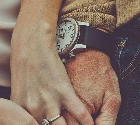 maos de homem e mulher estão entrelaçadas em close na foto. Ela usa um anel no anular e ele um relógio de pulseira de couro preto