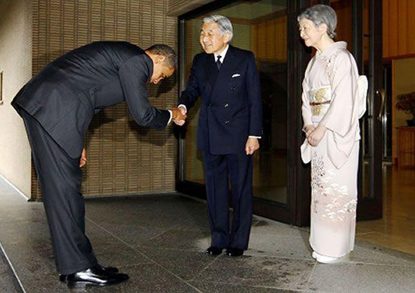 Presidente Barack Obama , vestindo terno escuro, em visita a Casa Imperial do Japão, ele é recebido honrosamente pelo Imperador Akihito do Japão e a Imperatriz Mitiko, onde Presidente Obama faz a reverência tradicional japonesa, curvando-se noventa graus o seu tronco. E o Imperador vestindo terno jaquetão preto , camisa branca e gravata preta, oferece a mão para o cumprimento tradicional ocidental.