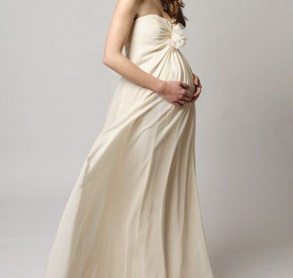 Moça grávida de aproximadamente 9 meses, com vestido de noiva simples, com cor creme, modelo tomara que caia, com tecido fluido que cai em camadas envolvendo seu corpo levemente de forma a deixar os movimentos livres e a barriga confortável.