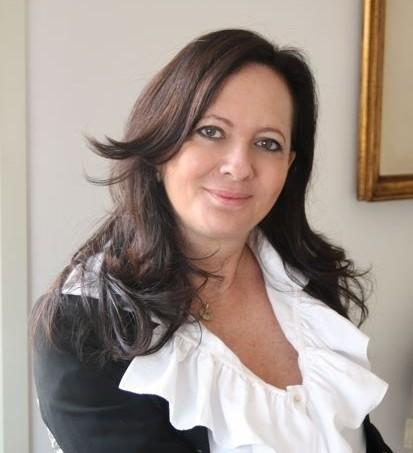 Mulher de cabelos longos e negros olha diretamente para camera. Ela veste uma blusa branca de babados e sobre a camisa um casaco de lã preta.