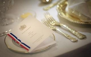 Detalhe de um cardápio com a descrição dos pratos e o Brasão da Família Real Britânica, colocado sobre o pratinho de pão em mesa de banquete do Palácio de Buckingham, mostra a simplicidade da toalha e louça brancas complementadas com requinte pelo talher de prata trabalhada.