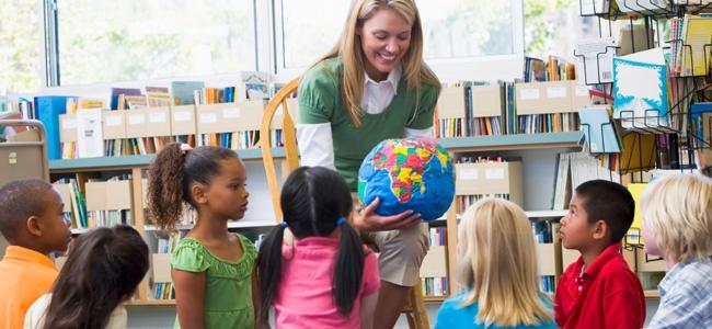professora bonita, vestida de camisa branca com uma camiseta verde por cima, mostra um globo bem colorido para sete crianças bastante interessadas.Eles estão em uma sala de aula repleta de livros.