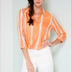 Modelo de cabelos castanhos trançados sobre os ombros usa uma bermuda branca, justa, na altura dos joelhos e uma camisa em seda coral clara, com listras brancas no sentido vertical. O efeito é de leveza e luminosidade.