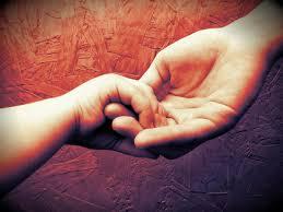 em um fundo avermelhado uma mão de adulto segura uma mão pequenina de bebê em gesto de acolhimento