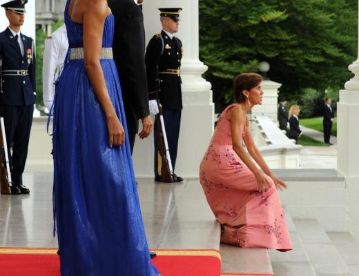 Senhora baixa, franzina,Chefe do Cerimonial da Casa Branca, usando vestido rosa longo, ao caminhar junto ao tapete vermelho, cai sentada na escadaria da Casa Branca, na frente de todos os fotógrafos do mundo todo, durante a recepção ao Presidente do México.