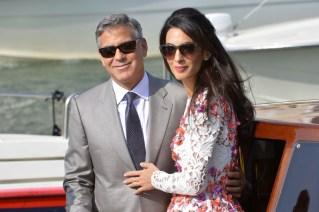 Ator George Clooney, de cabelos grisalhos e oculos escuros, vestido um lindo terno cinza claro , camisa branca e gravata cinza escuro, abraça lateralmente sua noiva , que usa óculos escuros também , usa vestido claro com desenhos de varios tons de flores, longos cabelos pretos - ambos estão no deck para embarcar no barco.