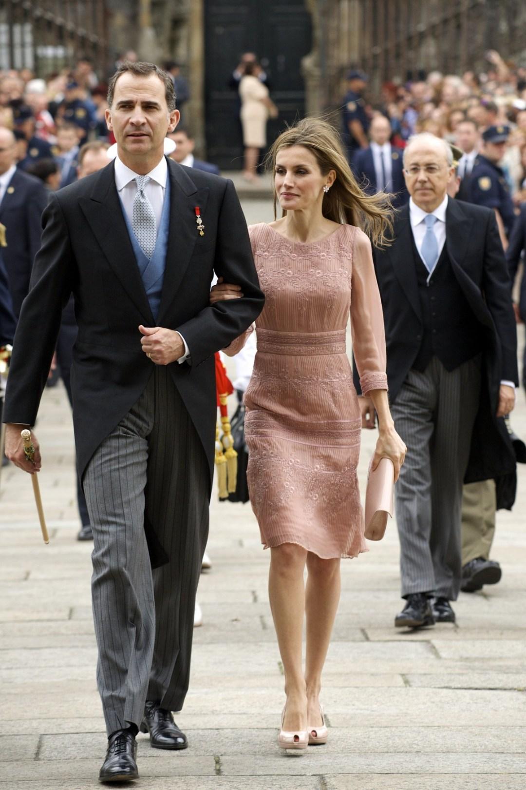 """O casal Real da Espanha, Rei Felipe VI e Rainha Letícia, participam de uma grande comemoração do Governo Espanhol, eles caminham juntos num corredor formado de milhares de pessoas. Ele veste uma casaca preta, com colete azul claro, gravata cinza e segura um bastão real , ela usa um vestido de organza, rosa claro e tom nude , nos pés sapatos de saltos altos plataforma de dois centímetros e abertos na ponta em estilo """"peep toe""""e segura uma bolsa no mesmo tom."""