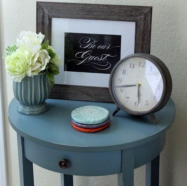 criado mudo azul. Em cima uma vasinho tb azul com flores frescas brancas, um relógio de ponteiros e um quadrinhos escrito be our guest