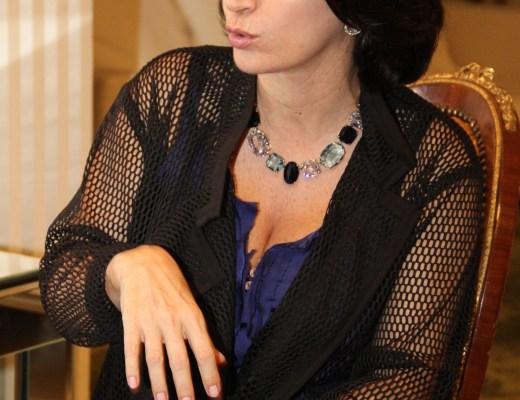 Claudia Matarazzo, durante sua palestra no Hipica Hall, em Brasilia , no final de setembro de 2014, está sentada numa cadeira chique, com pernas cruzadas, cabelos castanhos escuros, usa um colar com pedras azuis, varios tons, veste blusa azul bic, tecido leve, sobre ela um casaquinho escuro em tela suave, está com sua mão direita solta e pendente, como se estivesse gesticulando , a outra mão repousa sobre seu colo, sua saia preta de tecido, compõe um lindo visual