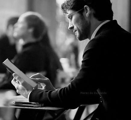 imagem em preto e branco, homem sentado numa mesa de bar, lendo um livro , ele jovem e usa barba
