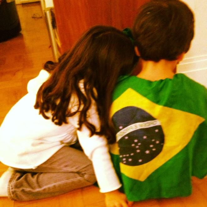 Duas crianças de costas , abaixadas, a menina de blusa branca e o menino tem uma bandeira do Brasil supere as costas