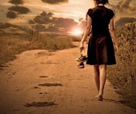 A imagem mostra uma mulher de costas, descalça, caminha numa estrada de terra , no por-do-sol, segurando um par de tênis na mão esquerda.