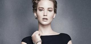 A atriz Jennifer Lawrence esta com um vestido preto e cabelos loiros e curtos penteados para tras. O destaque da foto é o brinco, em apenas uma orelha, com duas bolas douradas