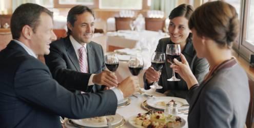 dois homens de terno e duas mulheres vestidas também com roupas sociais estão à mesa e brindam com taças de vinho