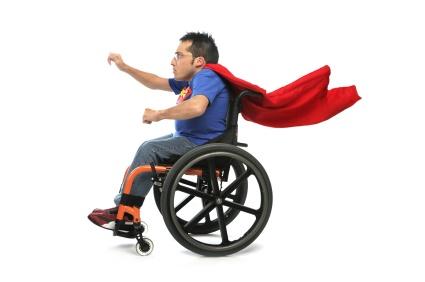pessoa usando um roupa de super-homem, camiseta azul está numa cadeira de rodas em alta velocidade e a capa vermelha voando junto ao pescoço