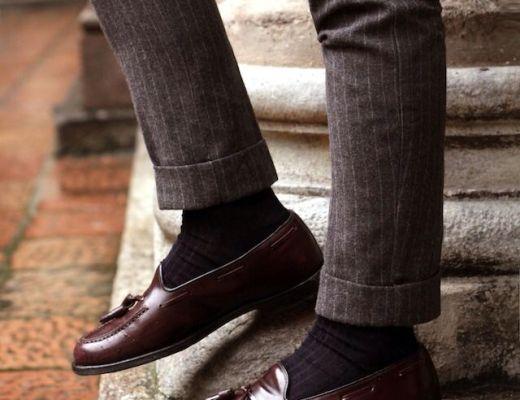 perna de homem, usando calça listrada, marrom, com frisos levemente claro, usa meia marrom escura, sapato de couro marrom, com detalhes pingente sobre o sapato da mesma cor. Ele está encostado numa coluna.