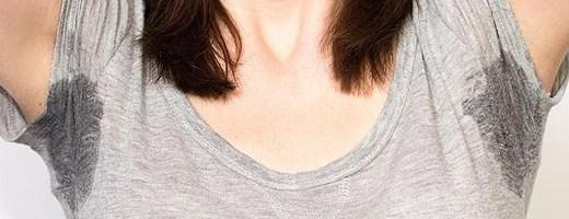 mulher com braços levantados vestindo camiseta cinza clara e com manchas de suor nas axilas