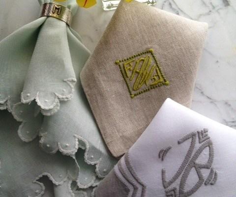 guardanapos de tecido de varias cores, verde claro bordado nas pontas, outro creme dobrado com monogramas bordados e o terceiro à direita branco com listras marrom claro bordadas nas pontas, todos sobrepostos numa mesa
