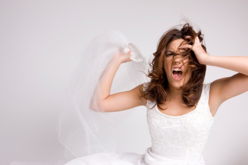 Moça vestida de noiva com cabelos castanhos na altura dos ombros está tirando o véu longo em um gesto de revolta e com expressão de quem está gritando. Os cabelos revoltos e a mão esquerda junto a testa reforçam a impressão de surtada