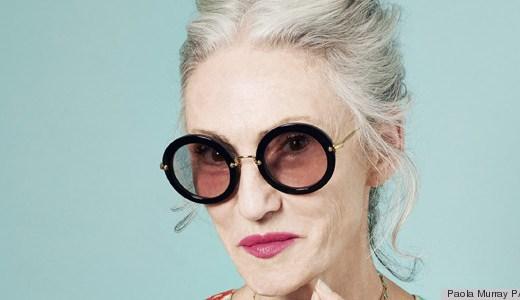 Daphne Selfe, modelo britânica , em foto do rosto, fundo verde, está com seus longos cabelos brancos presos em coque, seus óculos enormes, com lentes escuras, arredondadas, seu batom pink escuro, e tem um olhar divertido.