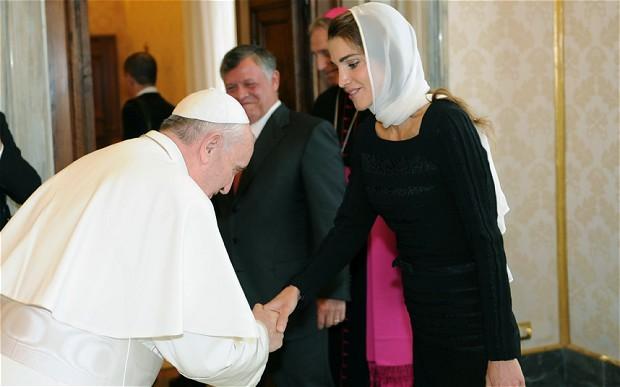 Papa Francisco, presta sua reverência ao recepcionar a Rainha Rânia da Jordânia, ao lado o Rei da Jordânia aprecia o justo e sorri, pela leveza do ato. Ela usa um lenço para cobrir sua cabeça, em sinal de respeito diante de um líder religioso.