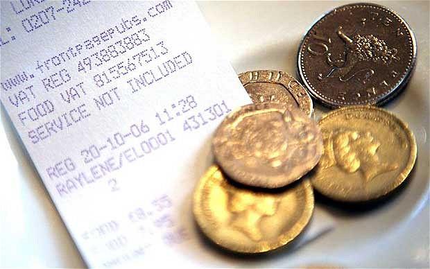 cinco moedas douradas em cima de uma conta de restaurante.