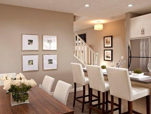Sala espaçosa aberta para a área da cozinha. As paredes são pintadas de bege claro com efeito de iluminar o ambiente e contrastam com o piso e a bancada da cozinha que são em madeira escura. As cadeiras da mesa da sala de jantar a esquerda da foto e as banquetas da bancada a da cozinha a direita são estofadas em tecidos crú aumentando a sensação de simplicidade e aconchego. Em uma das paredes ao fundo quatro quadros colocados geometricamente em um quadrado dão um toque moderno. Ao fundo do ambiente percebe-se um corrimão branco em sintonia com os armários brancos em madeira da cozinha que revestem o ambiente de serviço . No teto, luzes embutidas clareiam ainda mais o espaço.