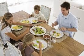 Familia sentada à mesa. A mãe está sentada ao lado da menina, de aproximadamente 9 anos e o pai ao lado do filho de aproximadamente 7 anos. Tem um prato na frente de cada um e no meio, uma travessa com salada. Aparenta uma refeição agravado e feliz