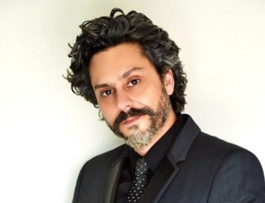 """Ator Alexandre Nero, com imagem do personagem da novela """"Império"""" da Rede Globo, está em imagem lateral, com cabelos, barba e bigode pretos grisalhos, veste camisa e paletó na cor preta, e grava preta com pequenas bolas brancas."""