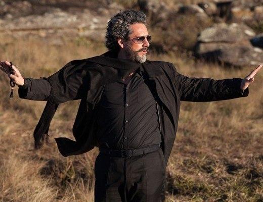ator Alexandre Nero, como personagem José Alfredo da novela Império, está no Monte de Roraima, veste calça, camisa e jaqueta na cor preta, está com os braços abertos em ambas direções, usa óculos escuros e seus cabelos grisalhos escuros.