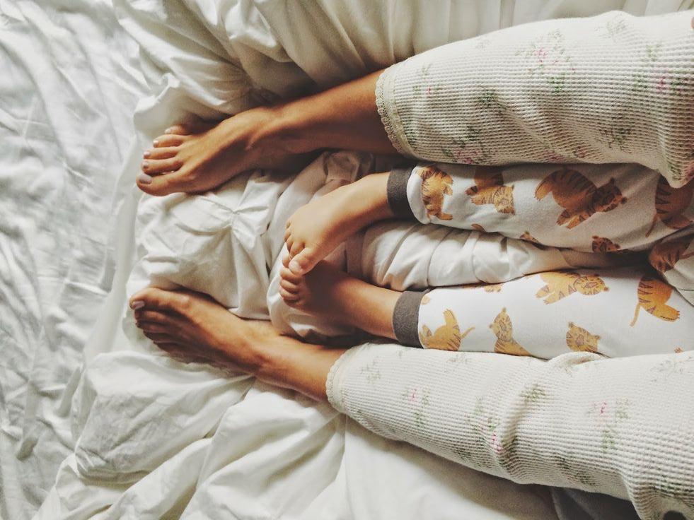 a imagem mostra um adulto envolvendo com as pernas o corpinho de uma criança de aproximadamente 4 anos de idade em uma cama aconchegante. A foto está cortada de modo a se perceber as pernas encaixadas - as da criança entre a da mãe. O curioso é que as duas estão girando o mesmo pé da mesma forma.