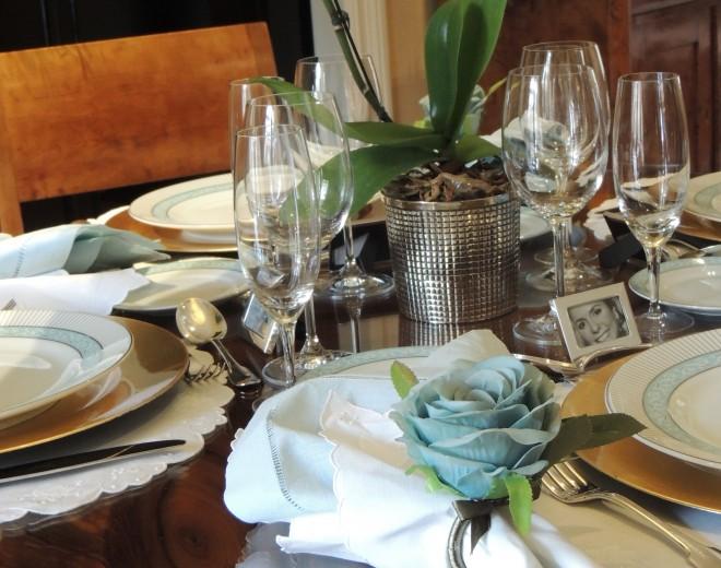 Mesa redonda em madeira, quatro lugares colocados, com jogo americano redondo, em tecido branco , com suaves bordados, o porta-guardanapo é uma rosa azul clara, com duas folhas verdes, o guardanapo é tecido na cor branca, os talheres em prata , além dos copos de água, taça de vinho branco e taça de champanhe , e ao centro um vaso em prata com uma orquídea branca. Detalhe que o lugar a mesa é marcado com um pequeno porta retrato com a foto do convidado.