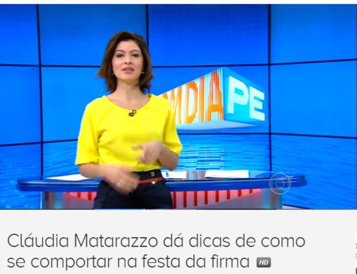 Apresentador do jornal Bom Dia Pernambuco vestindo saia preta e blusa amarela sem gola, faz a chamada da matéria de Claudia Matarazzo, ao fundo no cenário, uma enorme tela azul com os dizeres: BOM DIA , na cor laranja e a direita PE, em cor azul