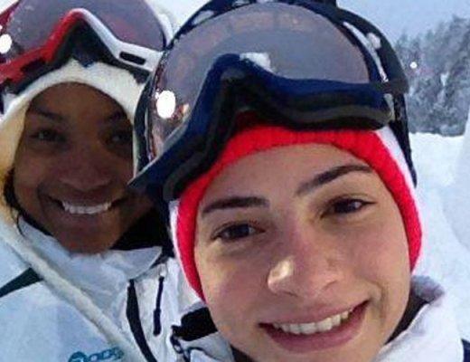 Lais de Souza, atleta brasileira, em imagem do rosto, está de sorrindo, com uma proteção na cabeça e um óculos para neve, ao fundo um outro esquiador também sorri.