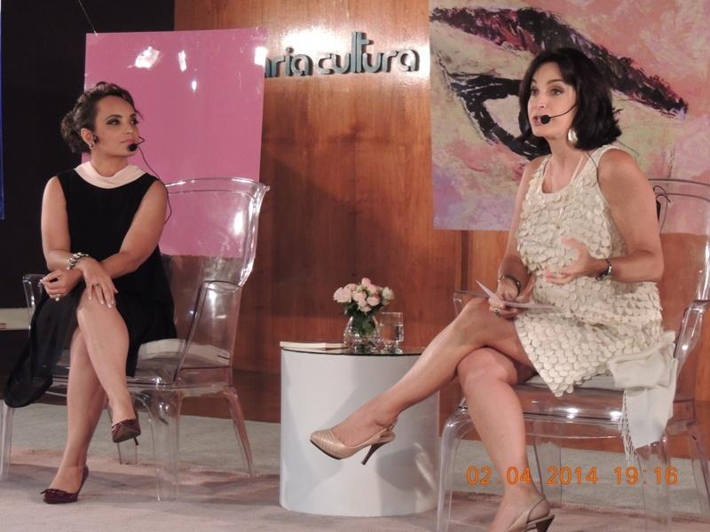 Claudia Matarazzo sentada numa cadeira num palco, durante uma entrevista, ela usa um vestido claro , com alças, está de pernas cruzadas e fala ao microfone, ao seu lado um mesa com um pequeno vaso de flores.