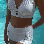 uma modelo de pele bronzeada, está para numa borda de piscina, com se estivesse saindo da piscina, ela usa um biquini branco, estilo Marilyn Monroe,