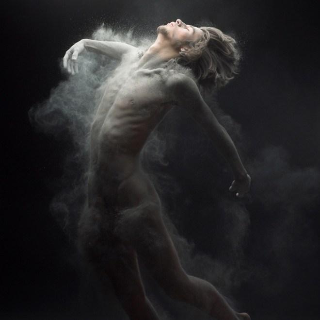 corpo de um homem desnudo, num ambiente escuro e sobre e rosto um luz clara ilumina a parte superior frontal. Ele gesticula como fôsse um salto frontal.