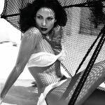 a atriz Jennifer Lopez, está sentada numa praia, ao fundo um guarda-sol trançado. Seu biquini tomara que caia, na cor branca e na parte de baixo da peça temos um grande laço