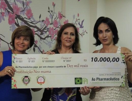 """Entrega do cheque da Campanha """"Formula do Bem, do Ao Pharmacêutico de Santos, na imagem Rosangela, Claudia Matarazzo seguram o cheque enorme constando o valor de 10.000,00 reais."""