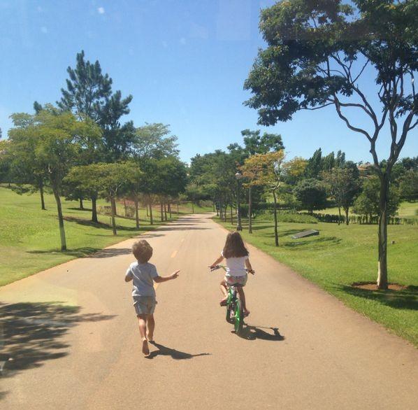 Numa manhã de sol, céu azul, numa rua de um parque, temos uma imagem de costas, de um menino corre junto a uma menina que anda de bicicleta.